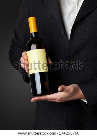 Man in suit holding white wine bottle isolated on black background