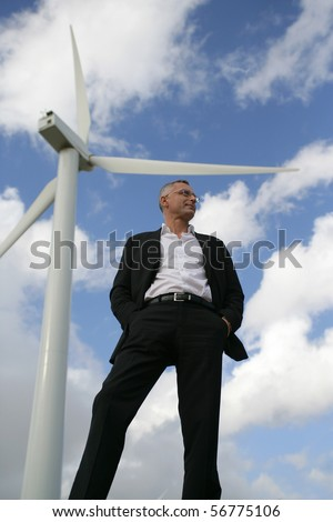 Man in suit in front of a wind turbine looking away