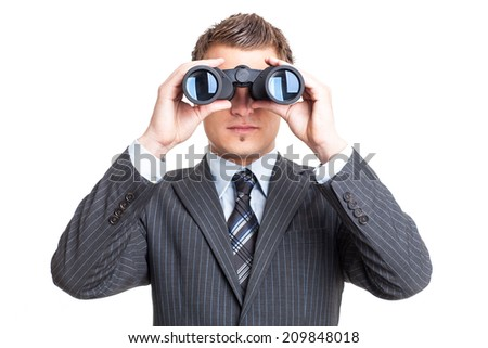 Man in suit looking through binoculars - stock photo