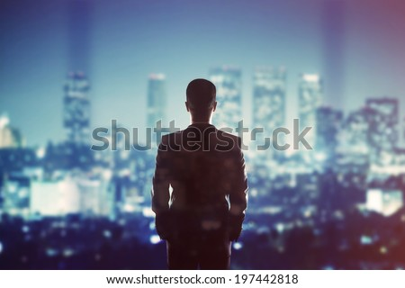 man in suit looking to night city - stock photo