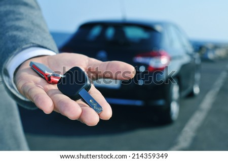 man in suit offering a car key to the observer, with a car in the background
