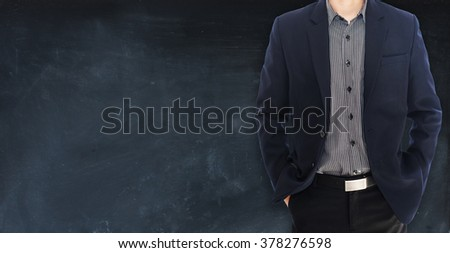 man in suit on a blackboard banner background - stock photo