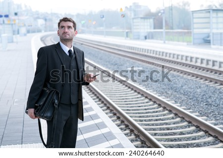 man in suit on business trip using his smartphone - stock photo