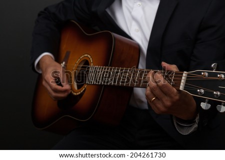 Man in suit playing guitar
