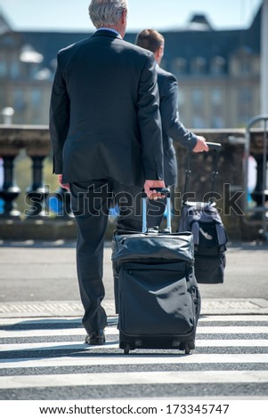 Man in suit pulling travelling suitcase on the street