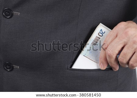 Man in suit putting a wad of twenty Euros banknotes in his pocket.  - stock photo