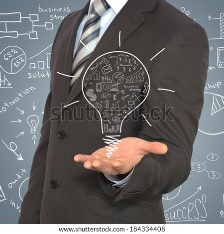 Man in suit raised his hand in front of him. Hand over are business sketches - stock photo
