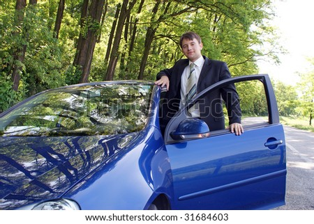 Man in suit ready to drive new car