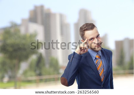 Man in suit self-confidence in front of skyscrapers - stock photo