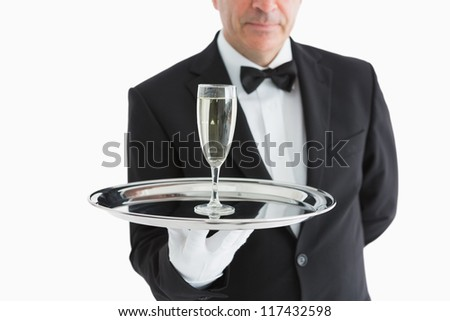 Man in suit serving glass with champagne on tray