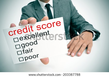 man in suit showing a signboard with the different ranges of the credit score: excellent, good, fair and poor - stock photo