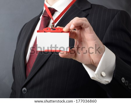 man in suit showing id or name badge  - stock photo