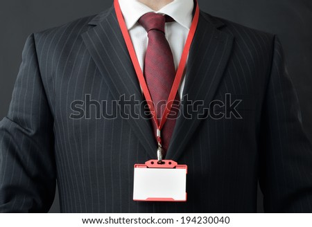 man in suit showing id or name badge