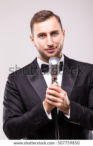 man in suit singing with the microphone and smile. Isolated on white background. Showman concept.