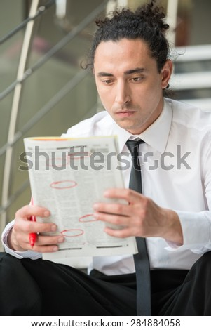 Man in suit sitting at stairs with  newspaper and searching job. - stock photo
