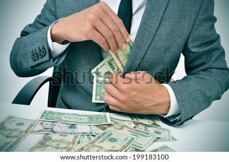 man in suit sitting in a desk full of dollar bills getting them in his jacket - stock photo