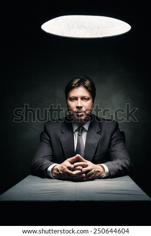 Man in suit sitting in dark room illuminated only by light from a lamp and looking in camera - stock photo