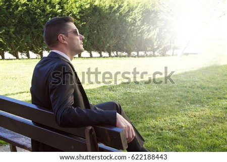 Man in suit sitting in the park