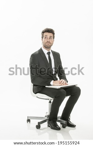 man in suit sitting with a laptop on his knees on isolated background