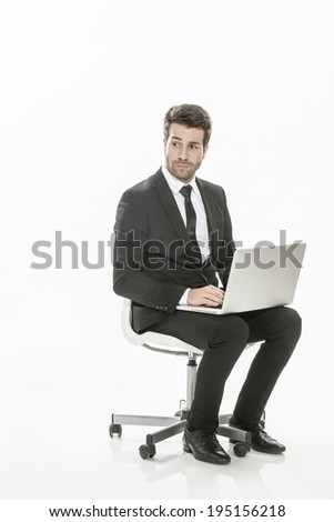 man in suit sitting with a laptop on his knees on isolated background - stock photo
