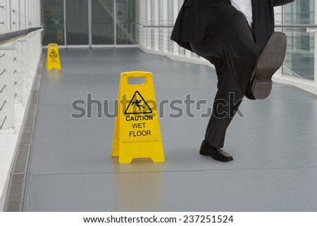 Man in suit slipping on wet floor with several warning signs - stock photo