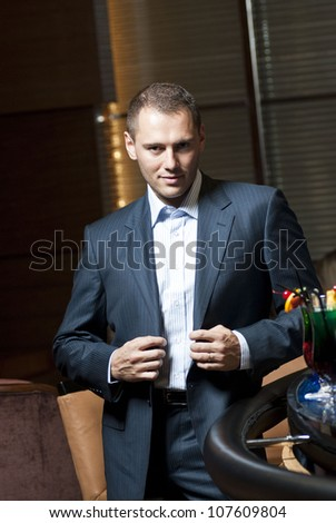 Man in suit standing  in the hotel lobby. - stock photo