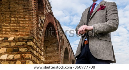 Man in suit standing next to an old building - stock photo