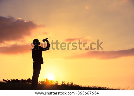 Man in suit throwing a paper plane.  - stock photo