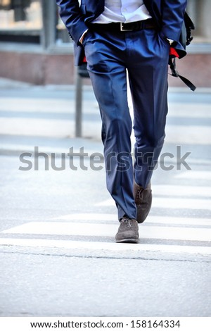 Man in suit with bag, on zebra crossing