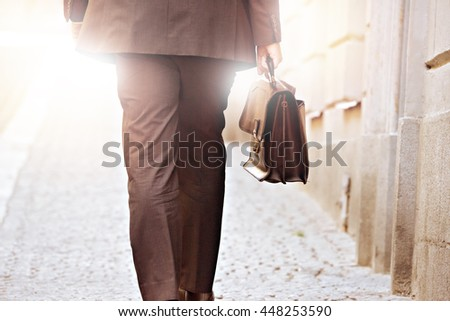 Man in suit with briefcase, walking on street - stock photo