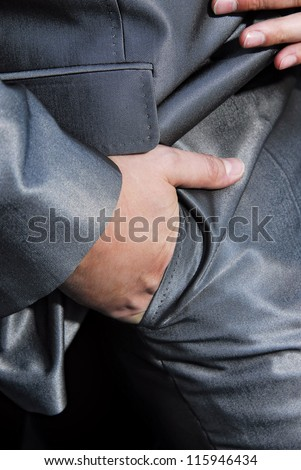 Man in suit with hands in pockets.