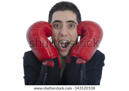 Man in suit with red boxing gloves with his hands on each side of his face shouting over white background.