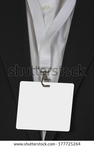 man in suite wearing a blank white pass card arround his neck - stock photo