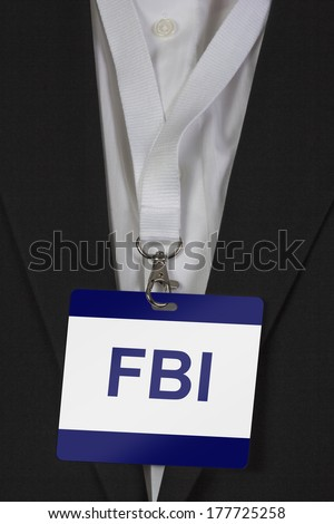 man in suite wearing pass labeled FBI arround his neck - stock photo