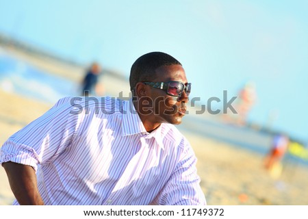 Man in sunglasses at the beach - stock photo