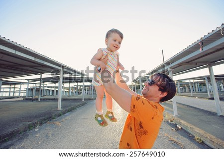 man in sunglasses holding girl in sunlight - stock photo