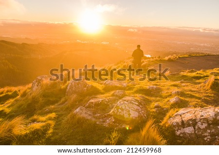 man in sunset at the top of the mountain - stock photo
