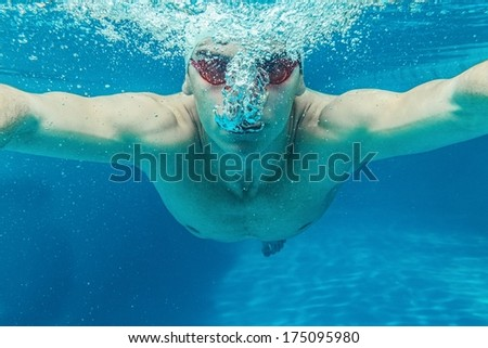 Man in swim cap and googles under water in swimming pool
