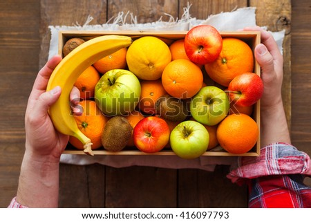 Man in tartan plaid shirt holds a box full of fresh fruits and a banana. Fruit harvest - apples, oranges, lemon, kiwi, banana. Rustic wooden table.