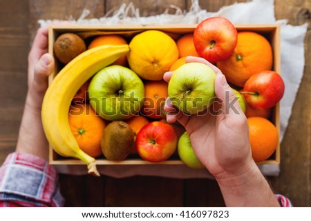 Man in tartan plaid shirt holds a box full of fresh fruits and a green apple. Fruit harvest - apples, oranges, lemon, kiwi, banana. Rustic wooden table.