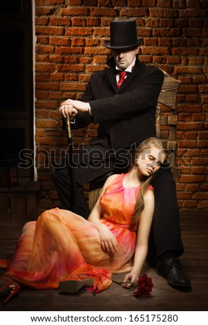 Man in the black coat, top hat and in a red tie and beautiful girl with rose - stock photo