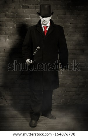 Man in the black coat, top hat and in a red tie on a wall background  - stock photo