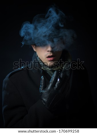 Man in the black trench coat smoking electronic hookah pen in the darkness - stock photo