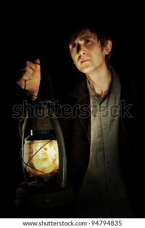 Man in the dark witn lantern in his hand