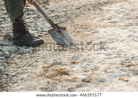 man in the desert, people search for water, military boots, shovel