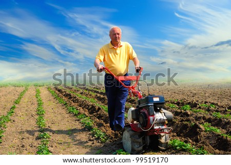 Man in the field with the motor cultivator - stock photo