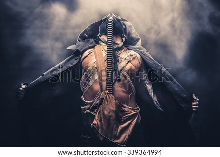 man in the gas mask in the hood, on the black background surrounded by smoke, with hands on the chest, survival soldier after apocalypse. - stock photo