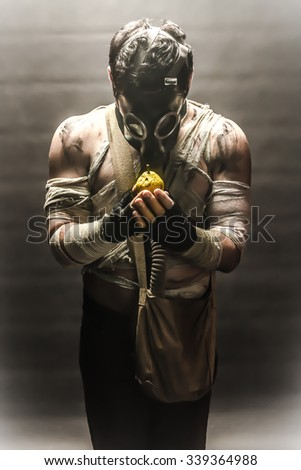 Man in the gas mask, on the black background surrounded by smoke, looking at the pear in his hands, survival soldier after apocalypse. - stock photo