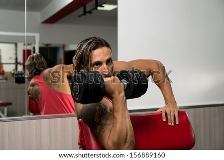 Man In The Gym Exercising Biceps With Dumbbells - stock photo