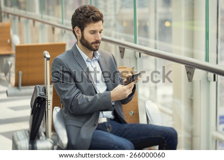 Man in the hall airport. Typing text message on mobile phone - stock photo